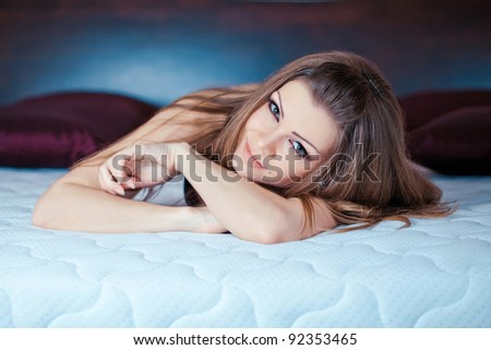 Portrait of beautiful young sexy woman laying on bed - stock photo