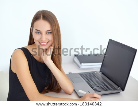 Portrait of beautiful young smiling business woman sitting at her workplace in office - stock photo