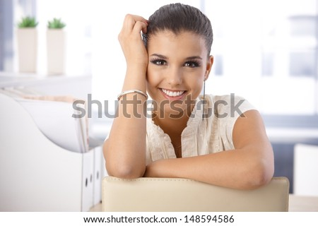 Portrait of beautiful young smiling girl in office. - stock photo
