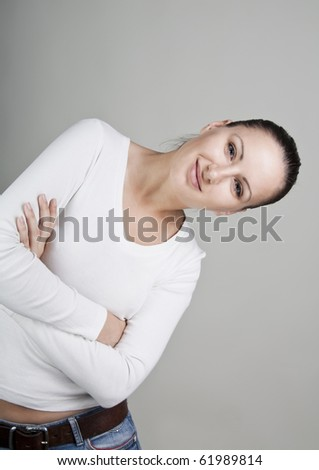 Portrait of beautiful young smiling woman, isolated on gray background