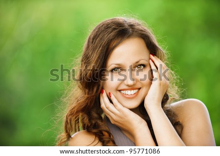 Portrait of beautiful young smiling woman stroking her pretty face at summer green park - stock photo