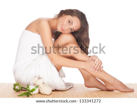 Portrait of beautiful young spa woman with healthy skin sitting and hugging her legs. Isolated on white background - stock photo