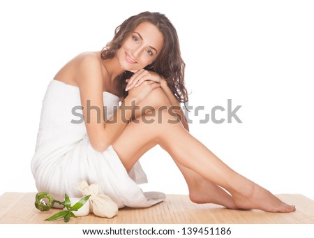 Portrait of beautiful young spa woman with healthy skin sitting and hugging her legs. Isolated on white background
