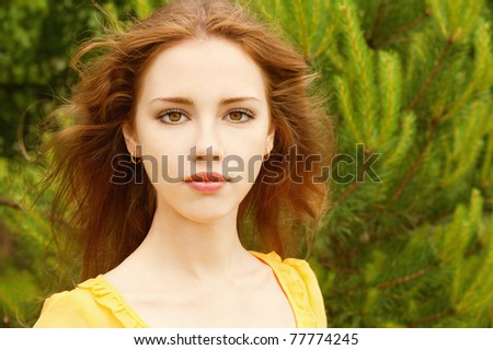 Portrait of beautiful young woman against green lawn. - stock photo