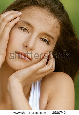 Portrait of beautiful young woman, against green of summer park. - stock photo