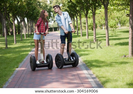 Portrait of beautiful young woman and handsome man. Girl and boy using segway and kissing. Green alley as background - stock photo