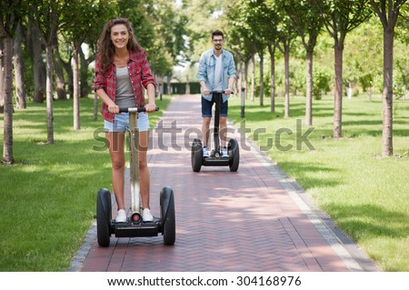 Portrait of beautiful young woman and handsome man. Girl and boy using segway. Girl smiling. Green alley as background - stock photo