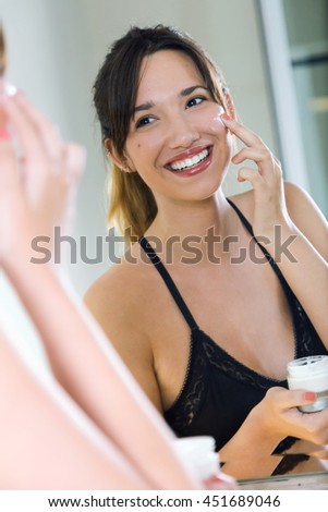 Portrait of beautiful young woman applying body cream on her face. - stock photo