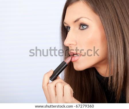 portrait of beautiful young woman applying lipstick - stock photo