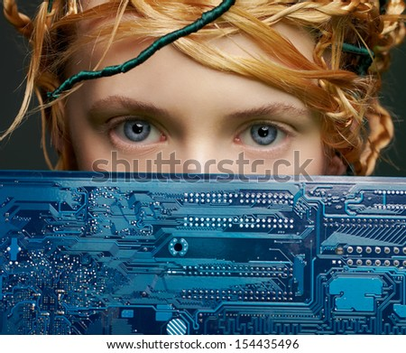 portrait of beautiful young woman closing half of her face with motherboard - stock photo