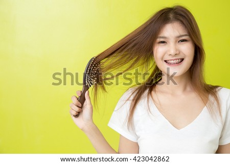 Portrait of beautiful young woman combing her hair.