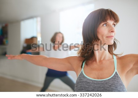 Portrait of beautiful young woman doing the warrior pose during yoga class. Yoga instructor performing Virabhadrasana position in gym. - stock photo