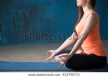 Portrait of beautiful young woman dressed in bright sportswear enjoying yoga indoors. Yogi girl working out in grunge interior with blue wall. Sitting in Lotus Posture. Close-up. Focus on hand - stock photo