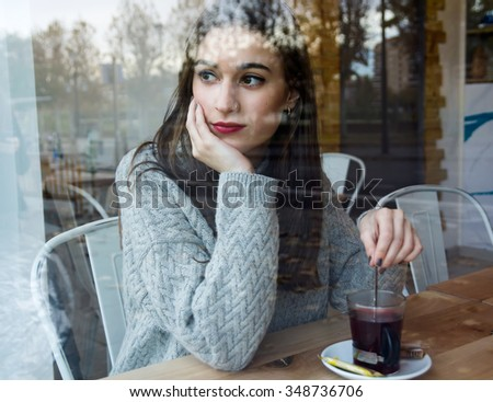 Portrait of beautiful young woman drinking tea in a coffee shop - stock photo