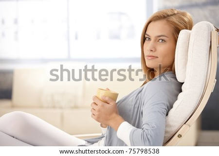 Portrait of beautiful young woman drinking tea in armchair, smiling.? - stock photo