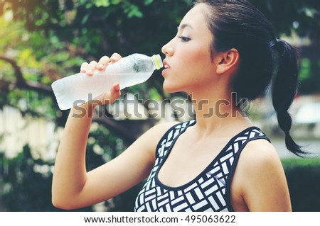 Portrait of beautiful young woman drinking the water after exercise.