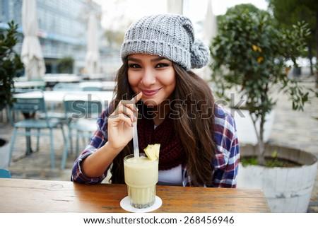 Portrait of beautiful young woman enjoying a drink, pretty girl sipping banana juice in coffee shop terrace - stock photo