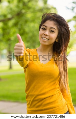 Portrait of beautiful young woman gesturing thumbs up in park
