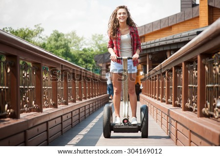 Portrait of beautiful young woman. Girl using segway, looking at camera and smiling - stock photo