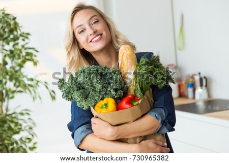 Portrait of beautiful young woman grocery shopping bag with vegetables at home.