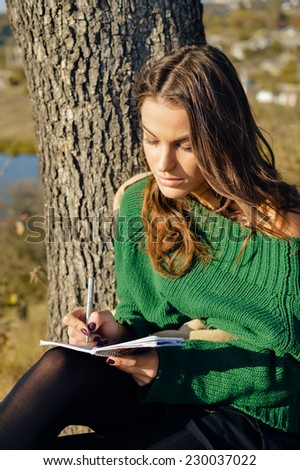 portrait of beautiful young woman having fun writing notes on sunny outdoors copy space background
