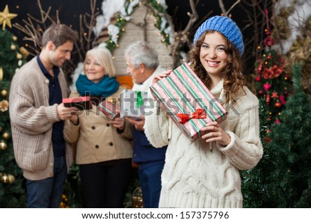 Portrait of beautiful young woman holding Christmas present with family standing in background at store - stock photo
