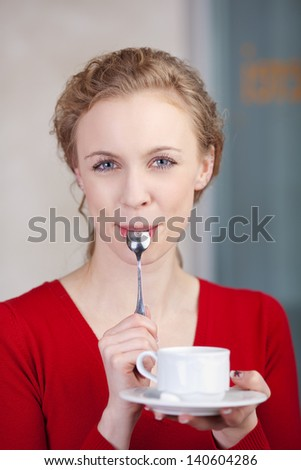 Portrait of beautiful young woman holding coffee cup while licking spoon in cafe - stock photo