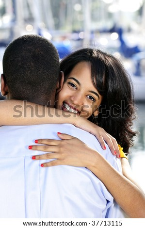 Portrait of beautiful young woman hugging boyfriend standing at harbor - stock photo