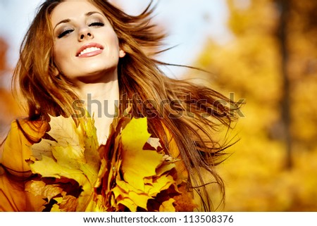 Portrait of beautiful young woman in autumn park. - stock photo