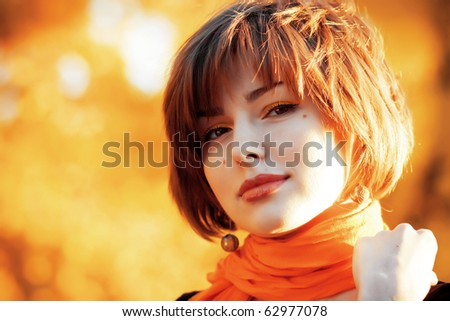 Portrait of beautiful young woman in autumn park - stock photo