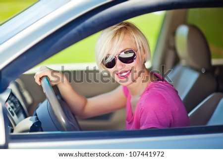Portrait of beautiful young woman in  car