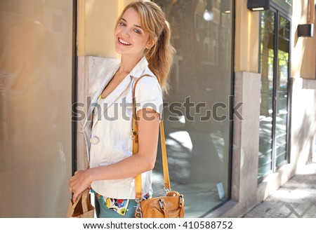 Portrait of beautiful young woman in city shopping street carrying paper bags by fashion store window, smiling looking at camera, outdoors. Consumer girl spending on holiday, lifestyle, exterior. - stock photo