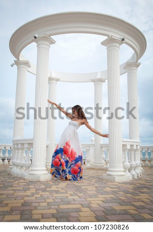 Portrait of beautiful young woman in colorful dress nearby the columns - stock photo
