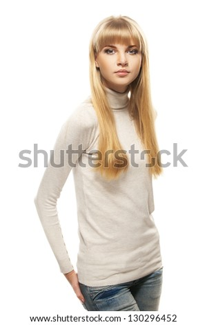 Portrait of beautiful young woman in gray sweater and jeans, isolated on white background.