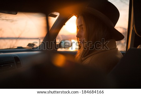 Portrait of beautiful young woman in hat, on the passenger seat in the car. - stock photo
