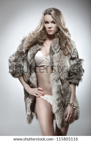 portrait of beautiful young woman in lingerie and fur coat posing against grey background