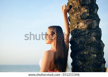 Portrait of beautiful young woman in pink bikini and sunglasses standing beside palm tree. Sideview of pretty girl smiling on summer blue sky background.