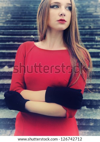 Portrait of beautiful young woman in red dress stay on stairs on the city street - stock photo
