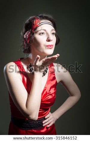 Portrait of beautiful young woman in retro dress sending air kiss. Pretty girl in 1920s styled red costume flirting on dark blurred background. - stock photo