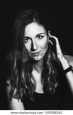 Portrait of beautiful young woman in studio on black background. Black and white.