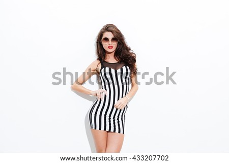 Portrait of beautiful young woman in sunglasses and striped dress over white background - stock photo