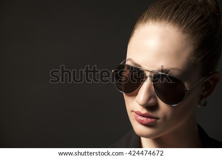Portrait of Beautiful young woman in sunglasses on black background