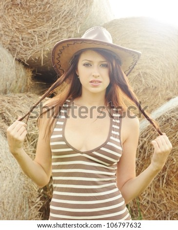 Portrait of beautiful young woman in western hat - stock photo