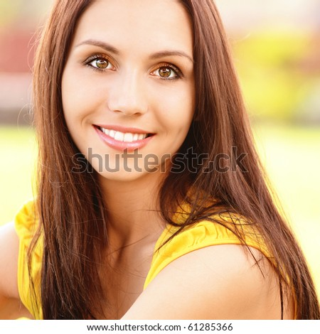 Portrait of beautiful young woman in yellow vest against green lawn. - stock photo