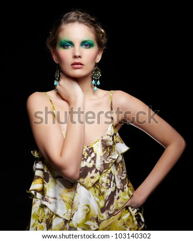 portrait of beautiful young woman ind summer dress with green and blue eye shade make up touching neck