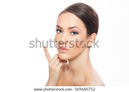 Portrait of beautiful young woman looking at camera applying face creme, isolated on white  - stock photo
