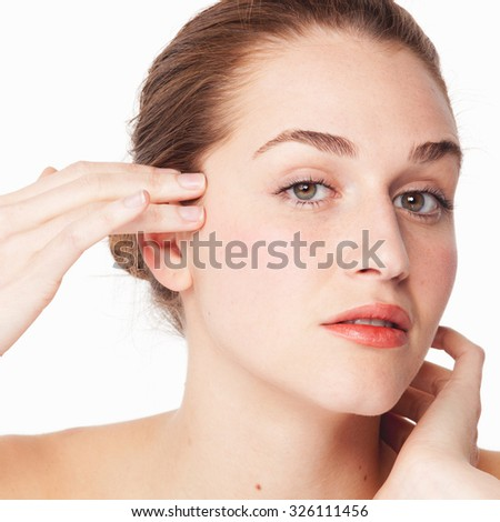 portrait of beautiful young woman looking at her eyes and skin for natural softness on white background - stock photo