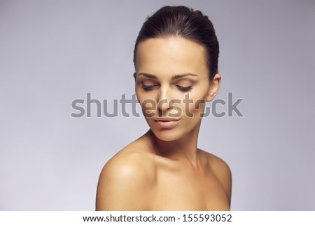 Portrait of beautiful young woman looking down at her shoulders against gray background. Sensual young female posing in gray background - stock photo