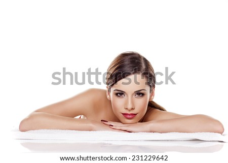 Portrait of beautiful young woman lying down on towel on a white background - stock photo