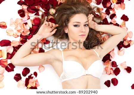 Portrait of beautiful young woman lying in rose petals. - stock photo